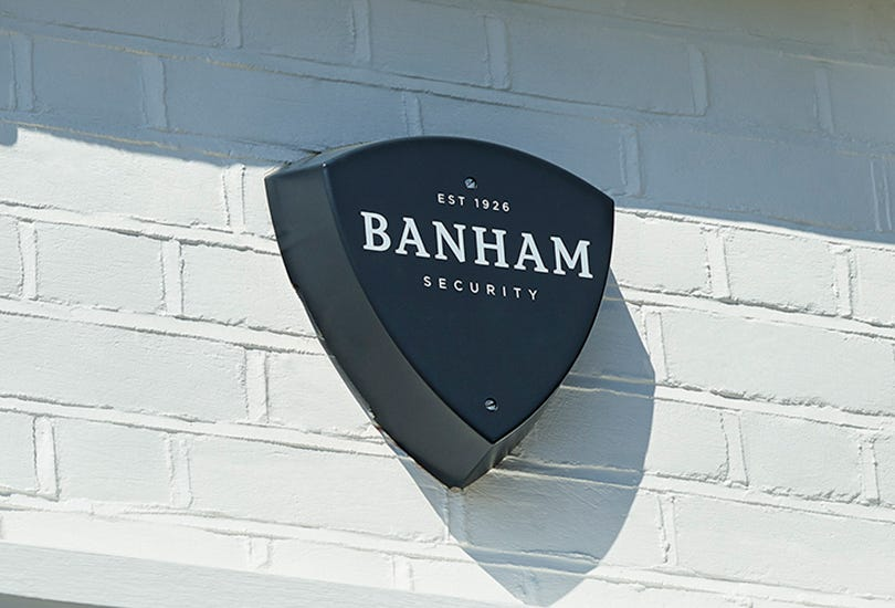 A Banham alarm that has been mounted on an external wall which reads: 'Est 1926 Banham Security'.