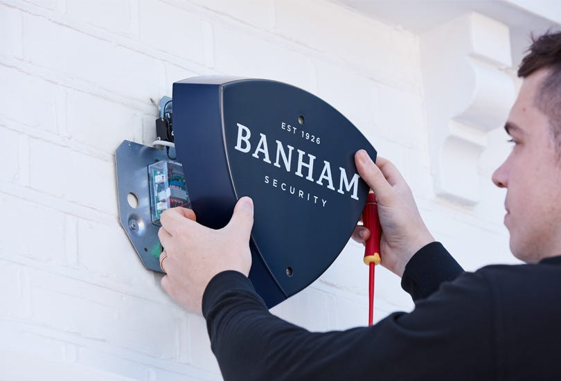 An engineer fitting a Banham burglar alarm system to an external wall.